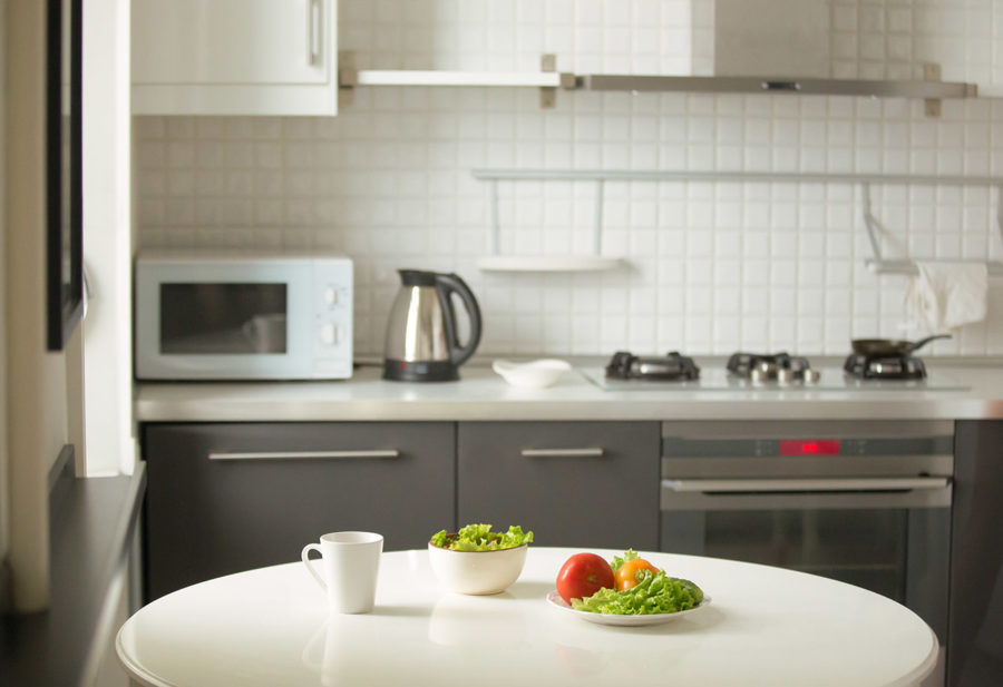 Modern kitchen, a white table with a mug and green salad